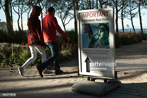 A couple walks next to sign informing them that the Statue of Liberty is closed due to the government shutdown in Battery Park on October 12 2013 in...