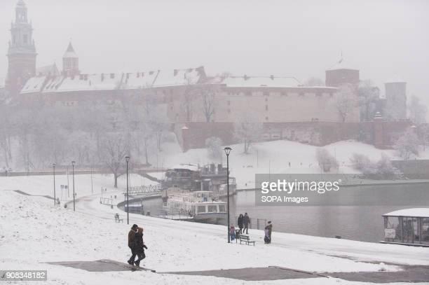 A couple walks next to Wawel Castle during winter in Krakow