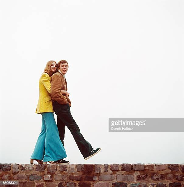 Couple walks on brick retaining wall