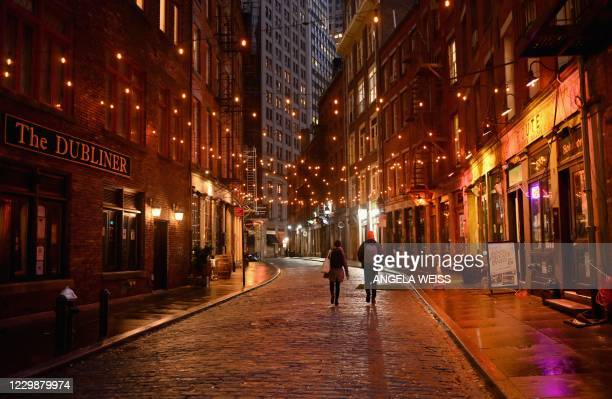 Couple walks on empty Stone Street, one of New York's oldest streets, in the Financial district of Manhattan on November 30, 2020 in New York City.