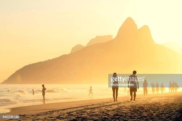 Couple walks on Ipanema´s sunset