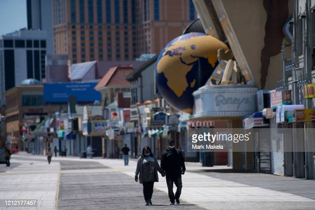 A couple walks on the boardwalk past shuttered stores during the coronavirus pandemic on May 7 2020 in Atlantic City New Jersey For the past 7 and a...