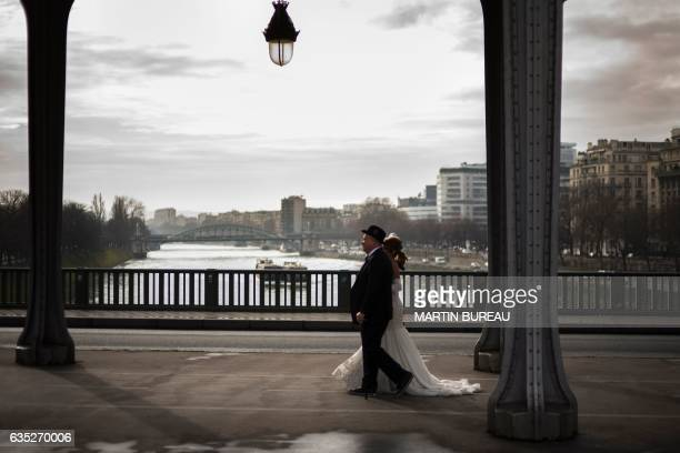 A couple walks on the Pont de BirHakeim bridge over the Seine River in Paris on Valentine's Day February 14 2017 / AFP / MARTIN BUREAU