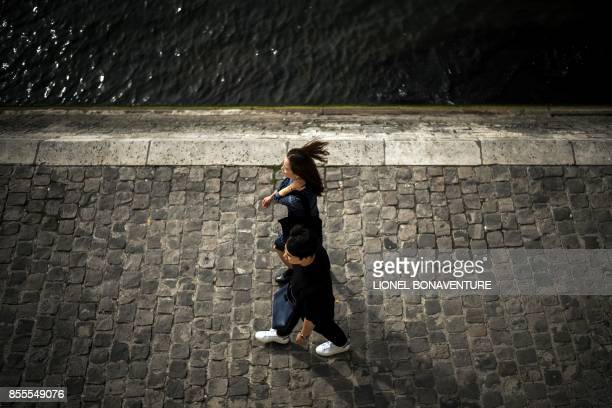 A couple walks on the Seine river bank on September 29 2017 in Paris / AFP PHOTO / Lionel BONAVENTURE