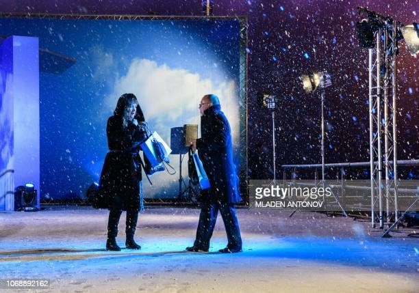 A couple walks out of the Moscow Theatre of Musical in a heavy snow in Moscow on December 5 2018