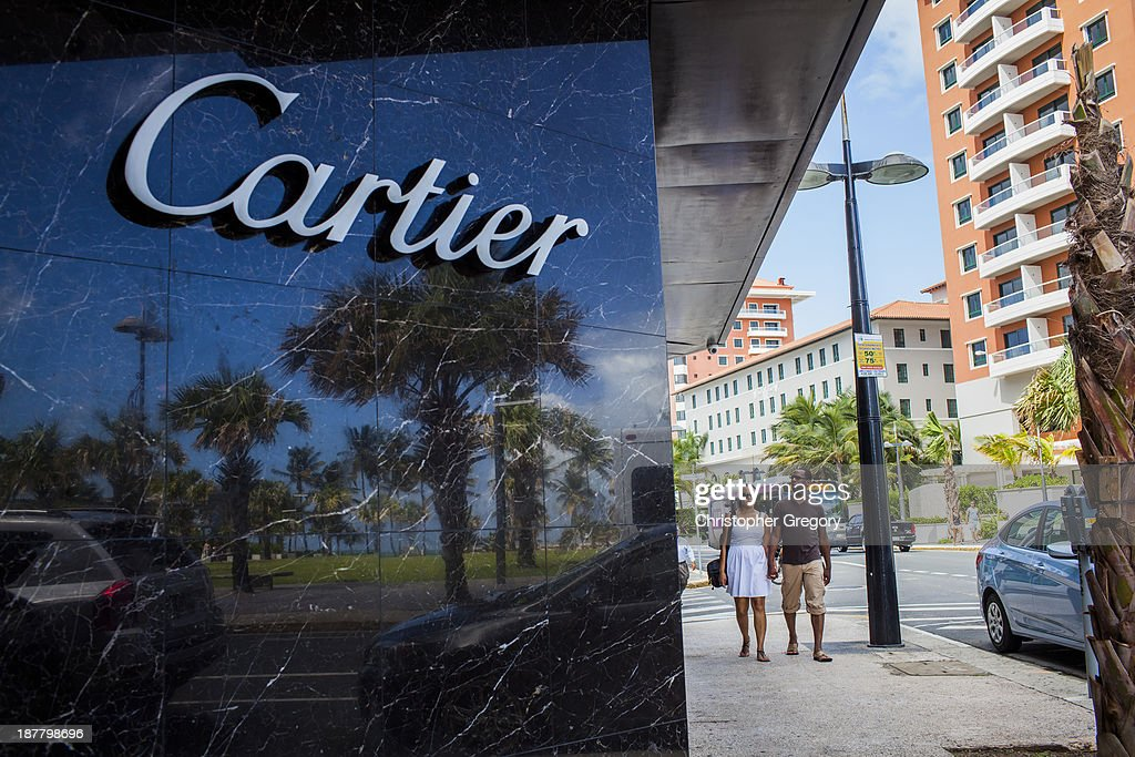 A couple walks past a Cartier store on November 12, 2013 in the Condado neighborhood of San Juan, Puerto Rico. The island territory of the United States, Puerto Rico, is on the brink of a debt crisis as lending has skyrocketed in the last decade as the government has been issuing municipal bonds. Market analysts have rated those bonds as junk and suspect it's 70 billion dollar debt might be unserviceable in the near future. With no industry other than tourism and the recent collapse of the real estate market, the way out is unclear.
