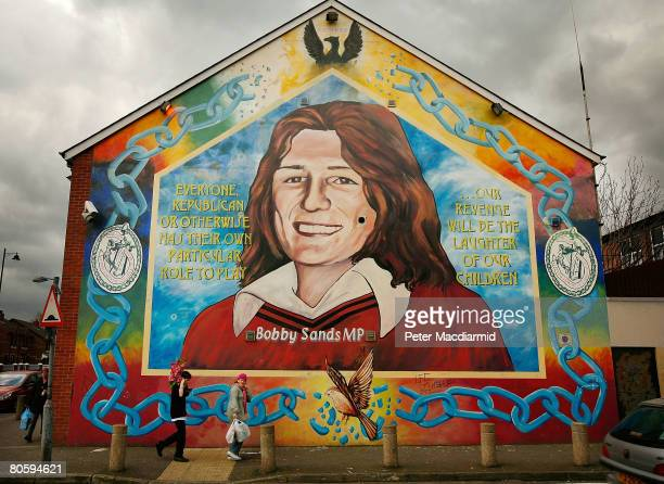 Couple walks past a mural depicting Bobby Sands in the Falls Road on April 10, 2008 in Belfast, Northern Ireland. In 1981, republican Sands died in...