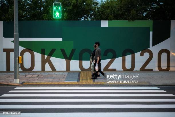 Couple walks past a poster for the 2020 Tokyo Olympics along a street in Tokyo on May 10, 2021.