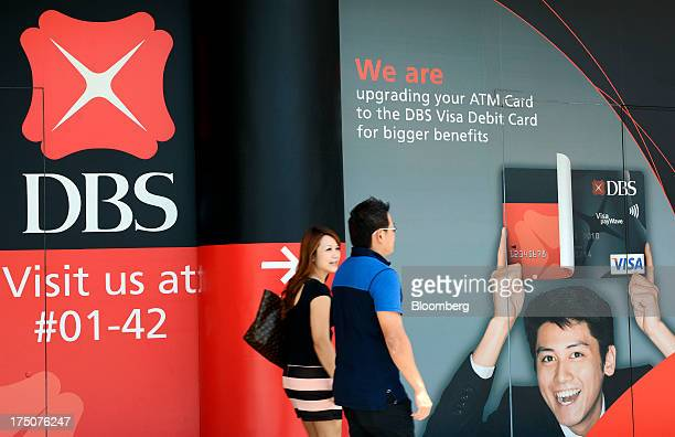 A couple walks past an advertisement outside a DBS Group Holdings Ltd bank branch in Singapore on Wednesday July 31 2013 DBS Southeast Asia's largest...