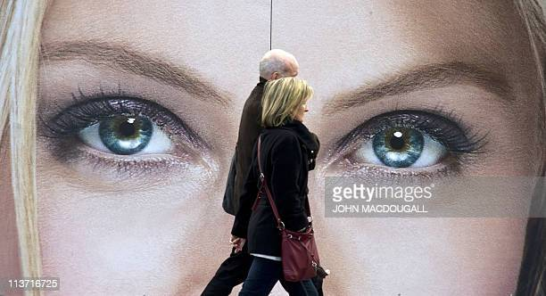 A couple walks past an advertising billboard for cosmetics featuring a closeup of a pair of women's eyes in Berlin on May 4 2011 AFP PHOTO / JOHN...