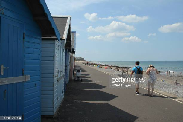 A couple walks past beach houses People enjoy the hot sun on Cromer beach as the weather in England went above 30 degrees for a third day running