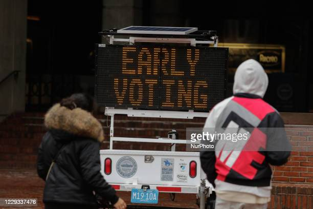 Couple walks past Early Voting direction at Boston CIty Hall Square in Boston, MA, 28 October 2020.