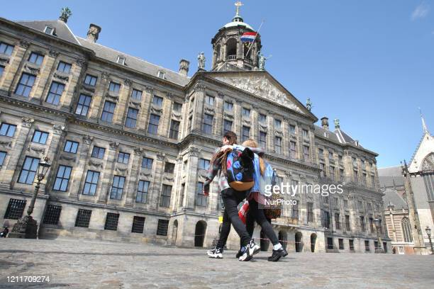 Couple walks past empty Dam square with National Dutch flag flying at half-mast at the Royal Palace during the Remembrance Day to celebrate 75 Years...