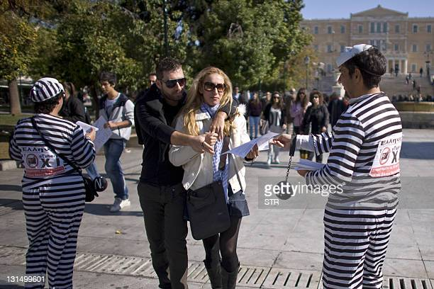 Couple walks past Greek demonstrators handing out leaflets as they protest against new electronic IDs which have been proposed as a measure to verify...
