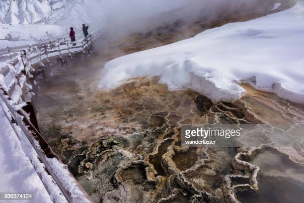 Couple walks past Intricate geothermal patterns at Yellowstone in winter