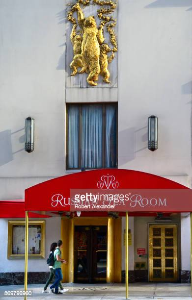 Couple walks past the entrance to the Russian Tea Room, a landmark Russo-Continental restaurant in Midtown Manhattan, New York, New York.