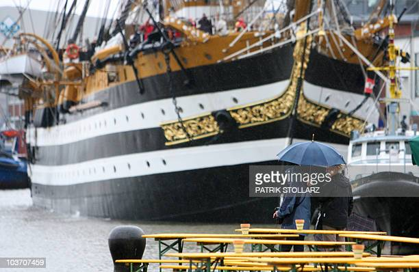 A couple walks past the Italian tall ship Amerigo Vespucci during the Sail 2010 sailing festival on August 29 2010 in Bremerhaven northern Germany...