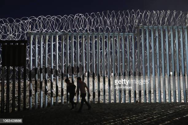 A couple walks past the recentlyfortified the USMexico border fence on November 18 2018 in Tijuana Mexico Parts of the migrant caravan have been...