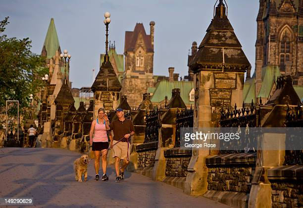 Couple walks their dog along Wellington Street on Parliament Hill on June 30, 2012 in Ottawa, Canada. Ottawa, the captial of Canada, is the fourth...