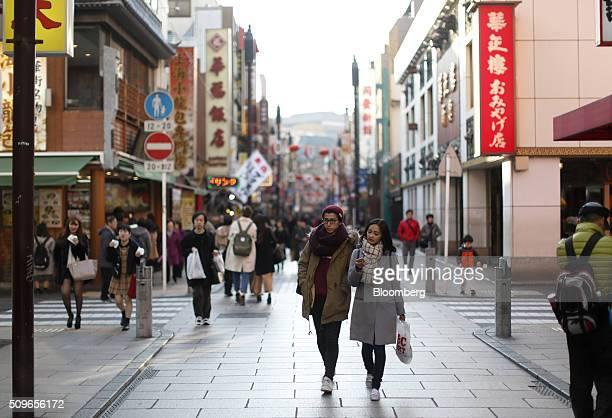A couple walks through a pedestrianized street in the Yokohama China Town area of Yokohama Japan on Tuesday Feb 9 2016 Japanese officials stepped up...