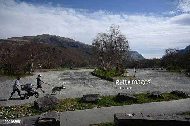 Couple walks through the empty car park of Llyn Padarn, a lake in Snowdonia near the village of Llanberis, north Wales on April 5, 2020 as the warm...
