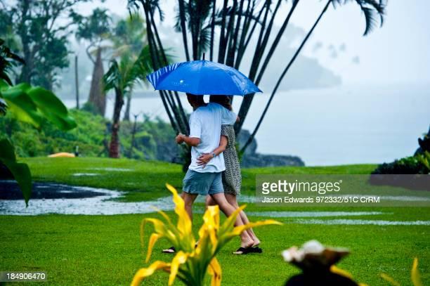 Couple walks through the rain arm-in-arm beneath an umbrella. Taveuni Island, Pacific Ocean, Fiji Islands.