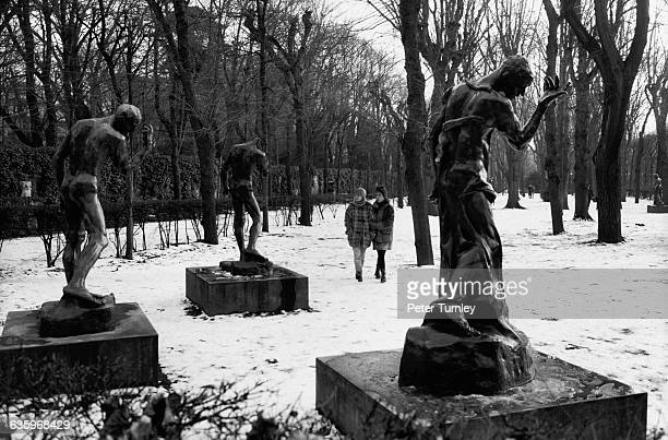A couple walks through the snowcovered grounds of the sculpture garden at the Rodin Museum in Paris