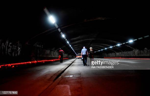 Couple walks through the tunnel after a vigil at the Love Parade Memorial on July 23, 2020 in Duisburg, western Germany, on the eve of the day...