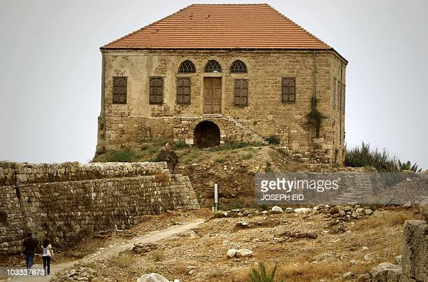 A couple walks towards nineteenth century house still standing near the Crusaders' Citadel in the Lebanese ancient port city of Byblos on August 10...