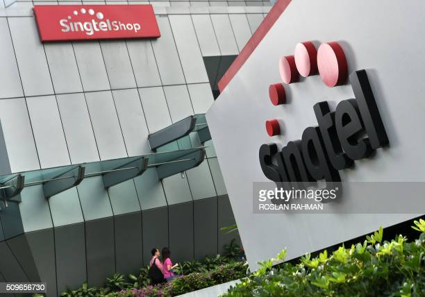 A couple walks towards the Singapore Telecommunications building in Singapore on February 12 2016 Singtel reported a 17 per cent fall in thirdquarter...