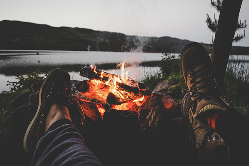 Couple warming their feet on camp fire 835067058