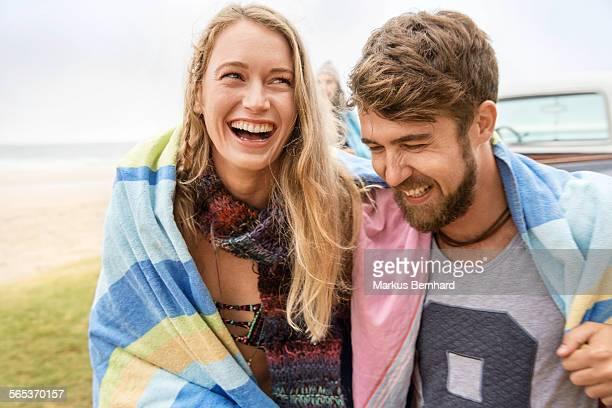 Couple warming up under blanket