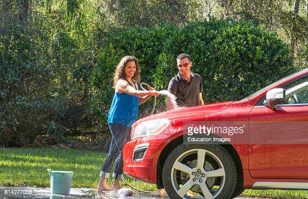 Couple wash car at home hispanic couple outside in sun red car fun together love Model Released, MR-12, MR-15.