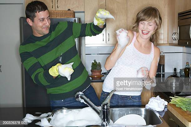 couple washing dishes in kitchen, laughing, playing with soap suds - couples showering together stock photos and pictures