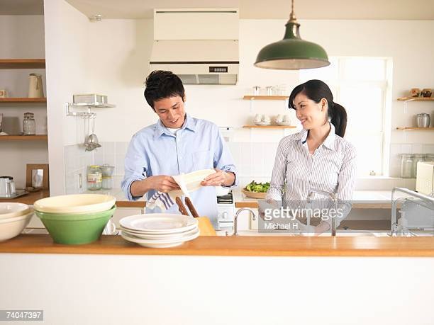 Couple washing dishes in kitchen