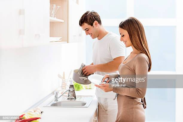 couple washing dishes. - couples showering stock pictures, royalty-free photos & images