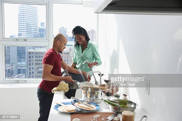 Couple washing pot in modern urban domestic kitchen