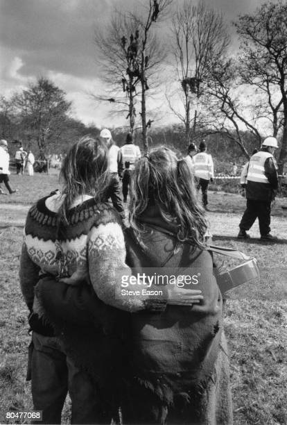 A couple watch as protestors take to the trees and the police move in during demonstrations against the construction of a bypass at Newbury Berkshire...