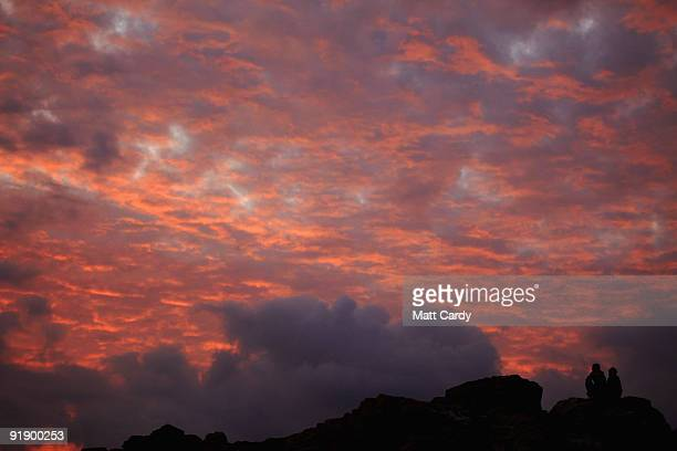 A couple watch as the sky as the sun sets over St Michael's Mount on October 14 2009 in Penzance England The tidal island which has houses shops and...