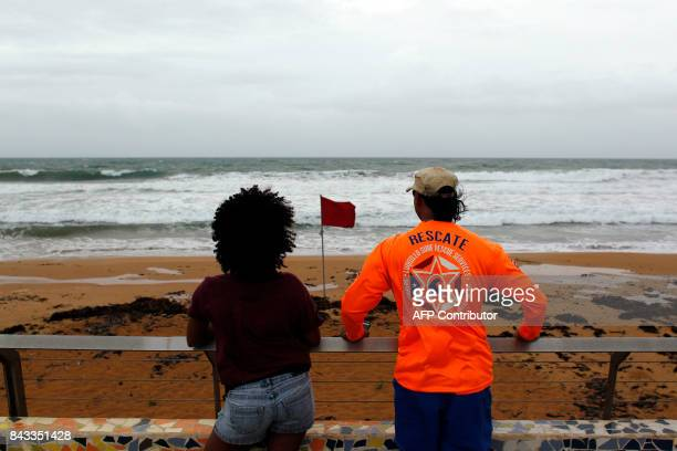 A couple watch from the shore at heavy surf as hurricane Irma approaches Puerto Rico in Luquillo on September 6 2017 Irma is expected to reach the...