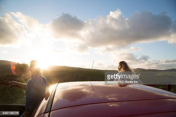 couple watch sunrise above hills beside car doors - eurasia stock pictures, royalty-free photos & images