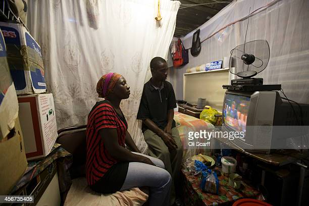 A couple watch the funeral of former South African President Nelson Mandela on television in their home in Soweto Township on December 15 2013 in...