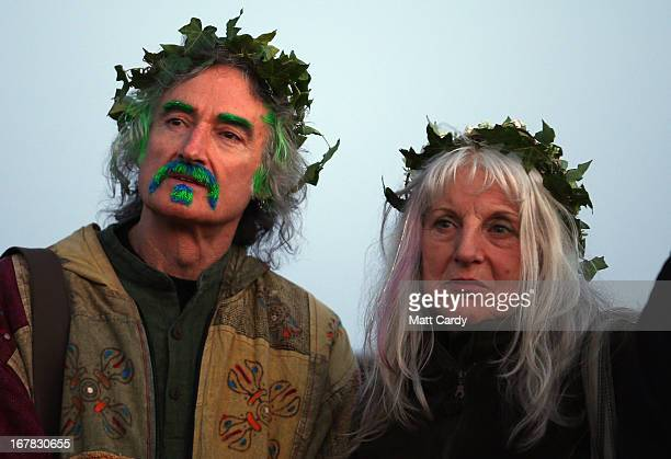 A couple watch the sun rise as they join in a Beltane dawn celebration service in front of St Michael's Tower on Glastonbury Tor on May 1 2013 in...