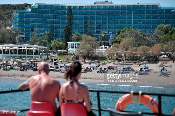 Couple watches a beach from a leisure boat off the Aegean island of Rhodes on August 29, 2020. - Rhodes island, one of the mass tourism Greek islands...