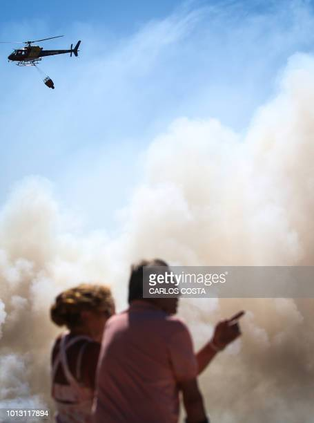 Couple watches an helicopter dropping water on a wildfire near Monchique, in Algarve, on August 8, 2018. - Spain and Portugal approached record...