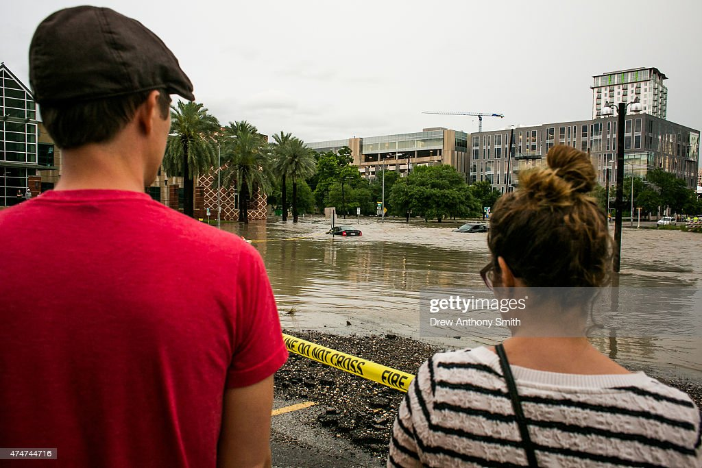 A couple watches flooding at Shoal Creek after days of heavy rain on May 25, 2015 in Austin, Texas. Texas Gov. Greg Abbott toured the damage zone where one person is confirmed dead and at least 12 others missing in flooding along the Rio Blanco, which reports say rose as much as 40 feet in places, caused by more than 10 inches of rain over a four-day period. The governor earlier declared a state of emergency in 24 Texas counties.