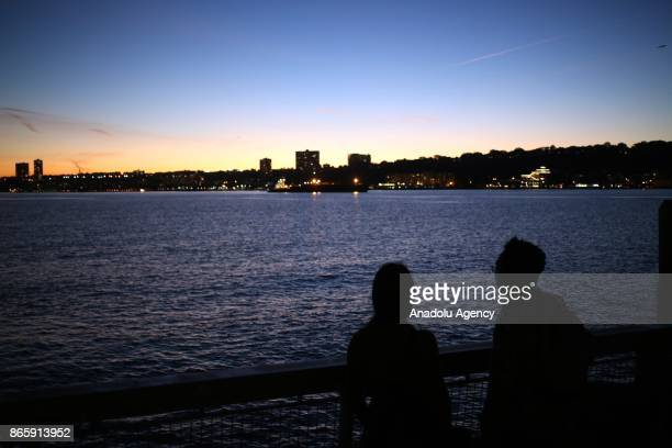 A couple watches the sunset at Hudson River of Harlem neighborhood of New York City United States on October 20 2017 116th street is long known for...