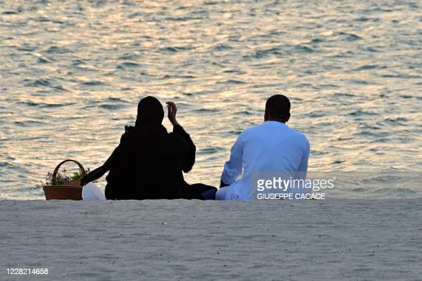 Couple watches the sunset at the beach in the Gulf Emirate of Dubai on August 26, 2020.