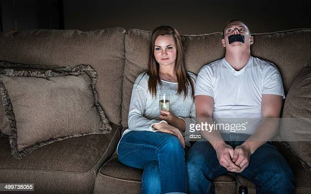 couple watches TV drama chick flick, girl and bored guy