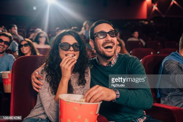couple watching 3d movie and eating popcorn - comedy film stock photos and pictures